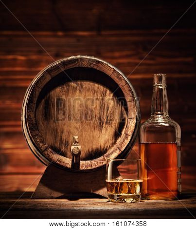Glass of whiskey, bottle and keg with ice cubes served on wooden planks with keg. Vintage countertop with highlight and a glass of hard liquor