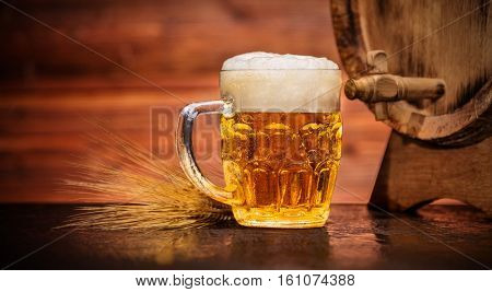 Glass of lager with old wooden keg, copyspace for text