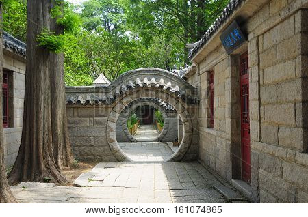 Curved archways cypress trees and chinese architecture within the Taoist Taiping Temple in Qingdao China in shandong province.