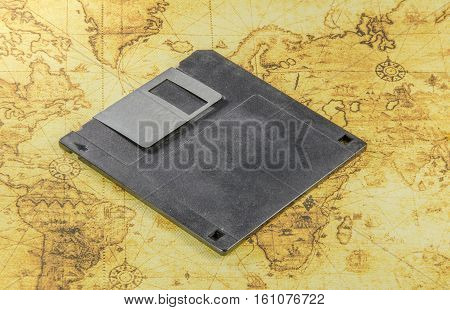dirty floppy disk on a old world map