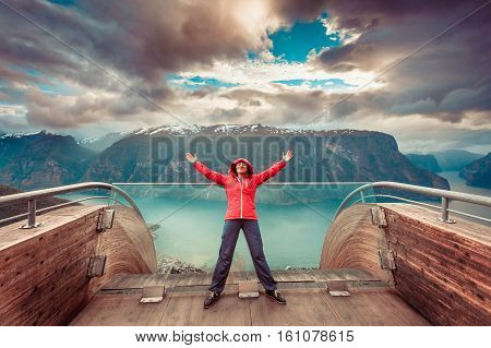 Tourist woman on Stegastein viewpoint enjoying Aurland fjord view with arms raised outstretched up Sogn Og Fjordane Norway