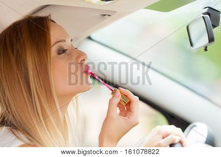 Distracted driver. Young attractive woman looking in rear view mirror painting her lips doing applying make up while driving the car.