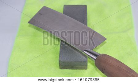 China cleaver knife sharpening on the gray stone. White background