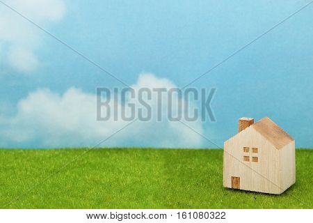 House on green grass over blue sky and clouds. Mortgage concept.