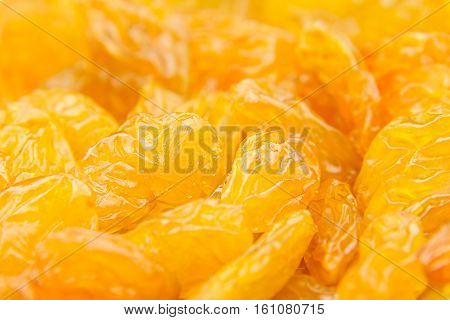 Raisins yellow closeup background. Heap of shiny golden yellow raisins dried fruit.