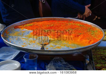 Kanafah on sale on the market. It is a Middle Eastern cheese pastry soaked in sweet sugar-based syrup