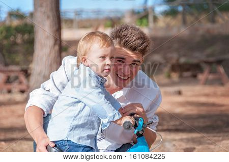The older brother played with a little brother. Adult spends time with the child. A young boy one year old child.