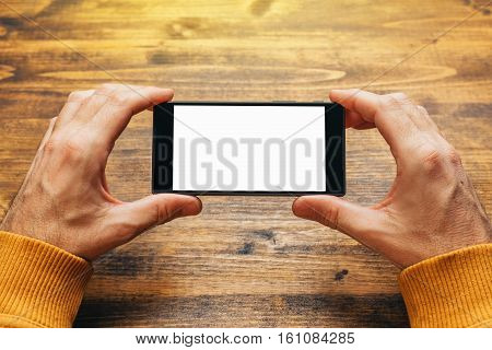 Man using smart phone in horizontal landscape orientation for streaming movies or browsing picture gallery blank screen as copy space