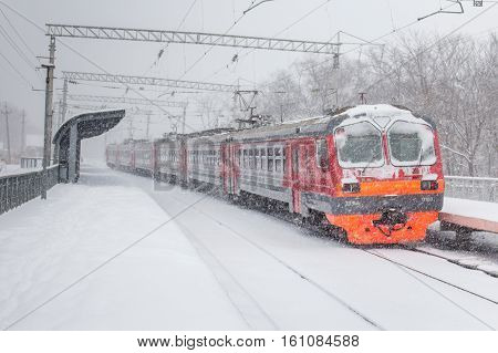 Electric train at station on a snowy day