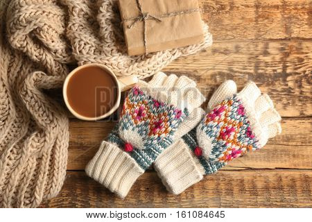 Knitwear and cup of coffee on wooden background