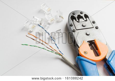 Crimper transparent connectors and ethernet cable on white background