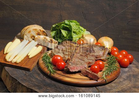 Grilled T bone steak mitRosmarin with tomatoes corn onions and asparagus garnished on a rustic wooden chopping board