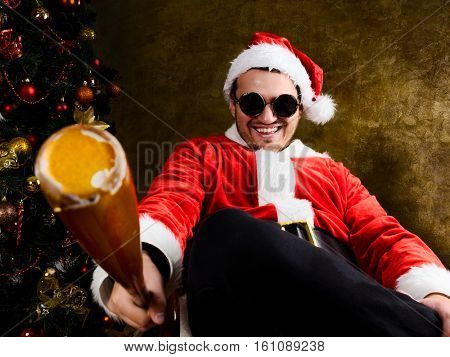 Bad Santa with baseball bat sitting indoors near Christmas or New Year fir tree
