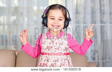 Happy Little Girl Wearing Headphones Is Dancing