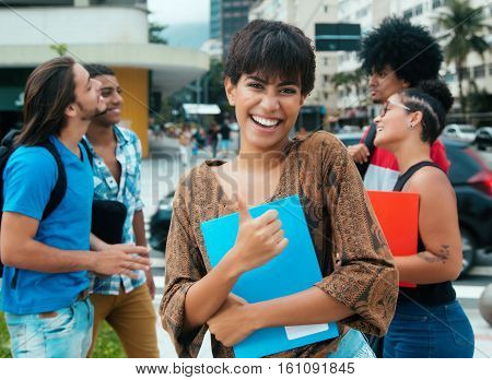 Laughing latin girl with group of multi ethnic students outdoor in city