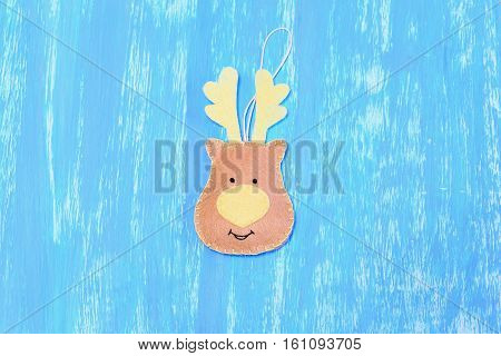 Sewing Christmas reindeer decoration of felt. Step. Beige felt reindeer decoration isolated on blue wooden background. Christmas easy craft instruction for children. Top view