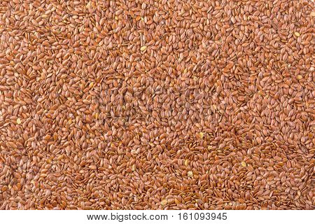 Background texture of roasted brown flax seed or linseed with healthy omega-3 fatty acids dietary fiber rich in oils and used to lower cholesterol
