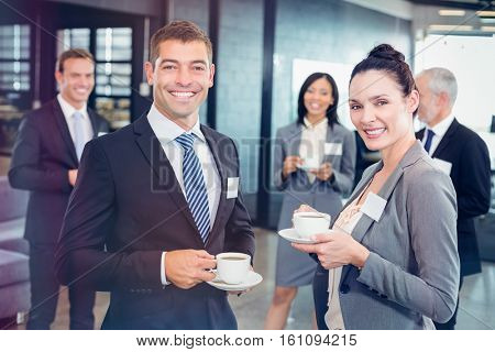 Portrait of businesspeople having tea and interacting during break time in office