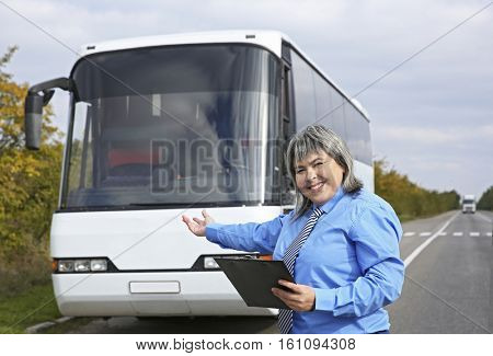 Female driver standing in front of bus