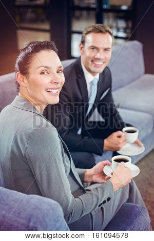 Portrait of businessman and businesswoman having tea during breaktime in office