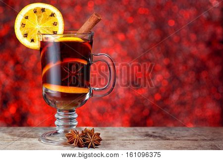 mulled wine with cinnamon stick orange slice and anise stars on wooden table with new year bokeh background. Christmas mulled wine with spices. Mulled wine with front of bright red bokeh lights background