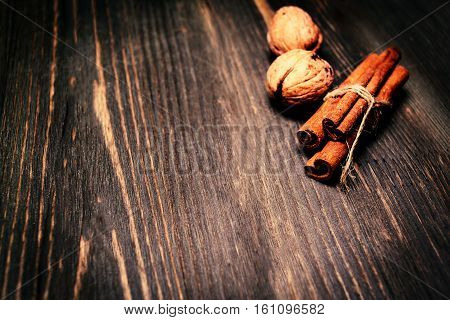 Cinnamon sticks and nuts on wooden background. Christmas winter spices with copy sace
