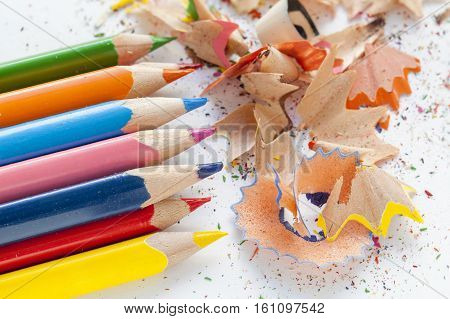 Sharpened colourful pencils and wood shavings on white piece of paper
