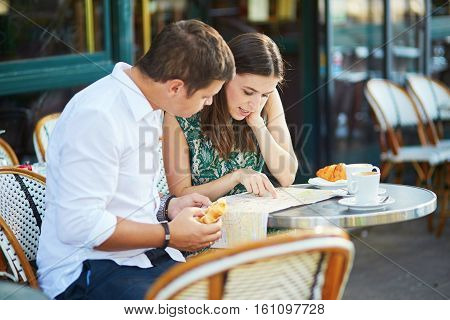 Young Romantic Couple With Map In French Cafe