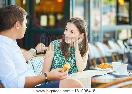 Young Romantic Couple In A Cozy Outdoor Cafe In Paris, France