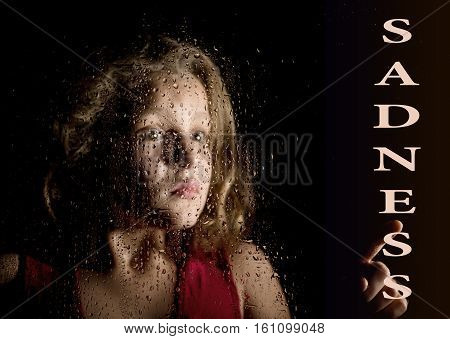 sadness written on virtual screen. hand of frightened young girl melancholy and sad at the window in the rain