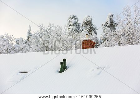 House roof with chimney at snowy winter day. Chimney with smoke.