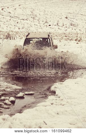 4x4 vehicles drive through the water splashing in winter season