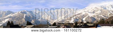 Hakuba mountain range in the afternoon early winter.  The steep terrain in the centre is between two ski resorts, Happo-One and Goryu.  Hakuba village houses in the foreground are on completely flat terrain.
