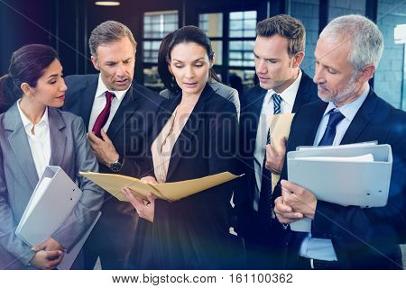 Lawyer looking at documents and interacting with businesspeople in office