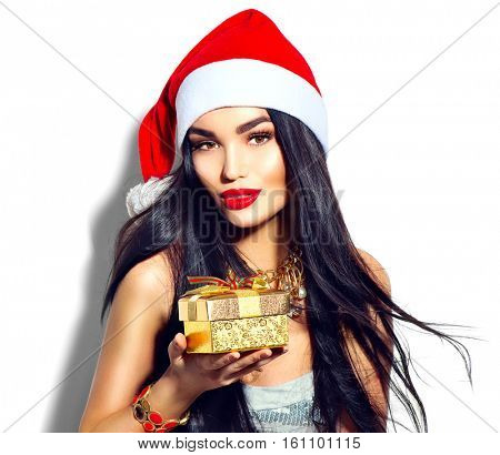 Beauty Christmas fashion model girl holding Xmas gift box. Long straight flying hair, red santa hat, holding gift box. Sexy brunette young woman portrait, fashionable party clothes and accessories