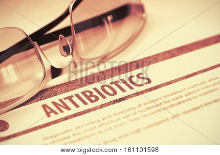 Diagnosis - Antibiotics. Medicine Concept on Red Background with Blurred Text and Spectacles. Selective Focus. 3D Rendering.