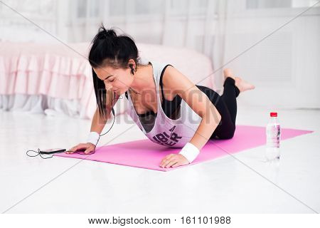 Fit sporty woman in headphones doing push ups home training listening music at smartphone concept crossfit fitness workout sport and lifestyle