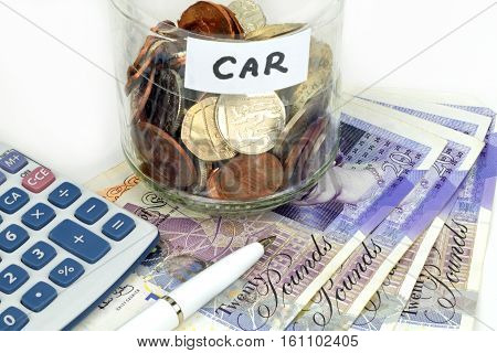 A car finance still life with jar of coins calculator notes and pen.