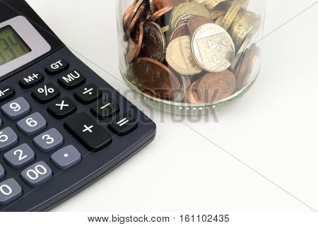 A jar of Sterling coins ans a calculator to represent Sterling finance.