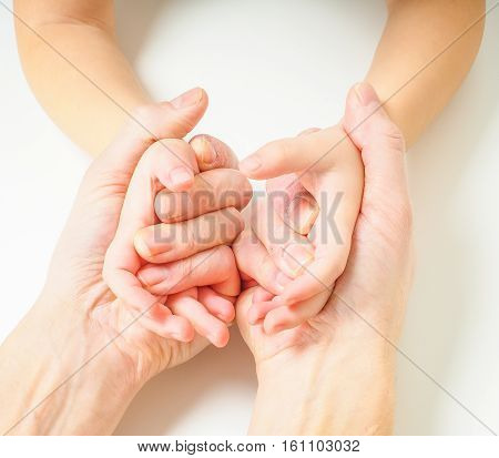 Toddlers Hands In Fathers Hands, Towards, On A White Table