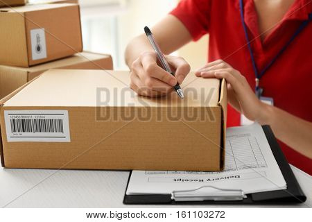 Courier hands writing on cardboard box at table