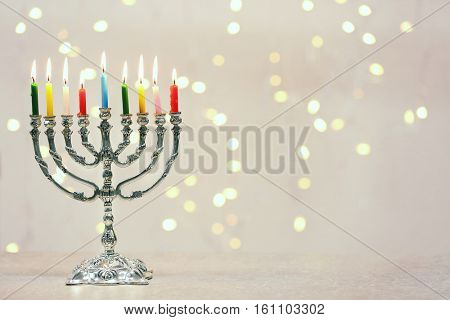 Menorah with colorful candles for Hanukkah on table against defocused lights
