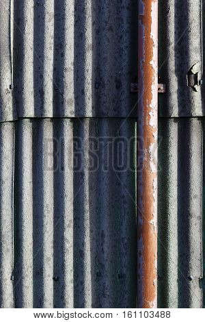 Old wall of corrugated asbestos material and a rusty drainpipe