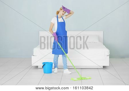 Pretty adult woman moping floor at home