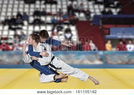 The two judokas fighters fighting men on fans background