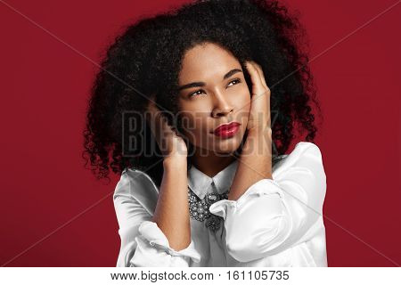 Black Woman Closed Her Ears From High Level Sound On Red Background