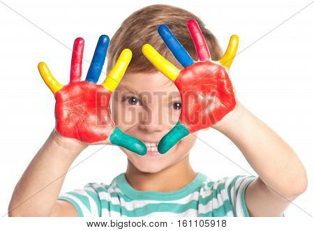 Eight year old boy with hands painted in colorful paints isolated on white background. Close up portrait of smiling kid ready for hand prints. Happy playful child looking at camera.