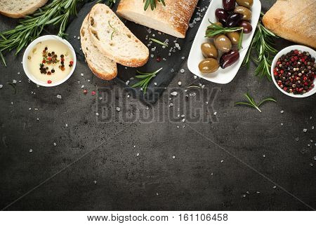 Italian ciabatta bread  on black slate board with herbs and olives, Top view Mediterranean Food background.