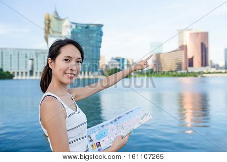 Woman using paper map and finger pointing far away