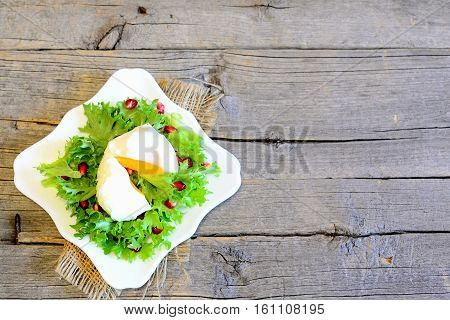 Poached egg, green lettuce leaves with pomegranate seeds and olive oil. Light salad on a plate on wooden background with copy space for text. Diet meal. Top view